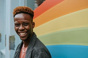 black man standing in front of rainbow colored mural