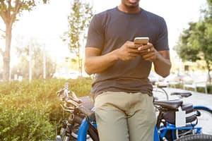 man on cell phone leaning on bike