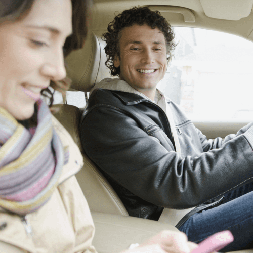 man and woman in car looking at phone