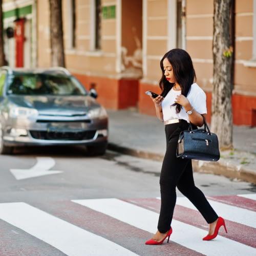 woman walking in crosswalk looking at phone